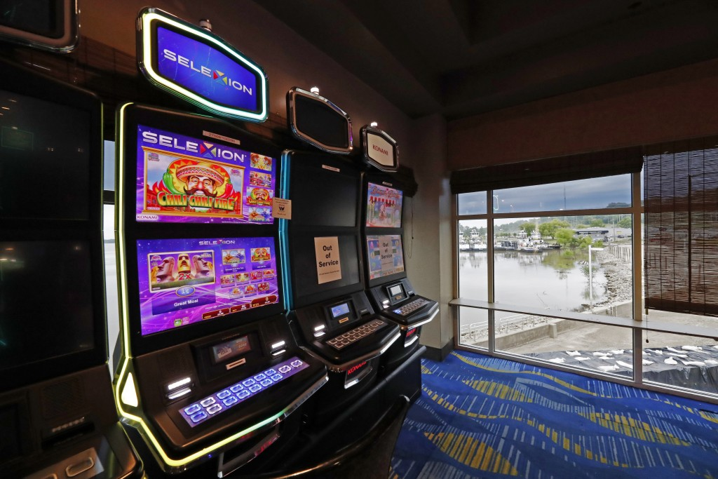 Two video slot machines await players while one in the middle sits out of service at the WaterView Casino and Hotel in Vicksburg, Miss., Thursday, May...