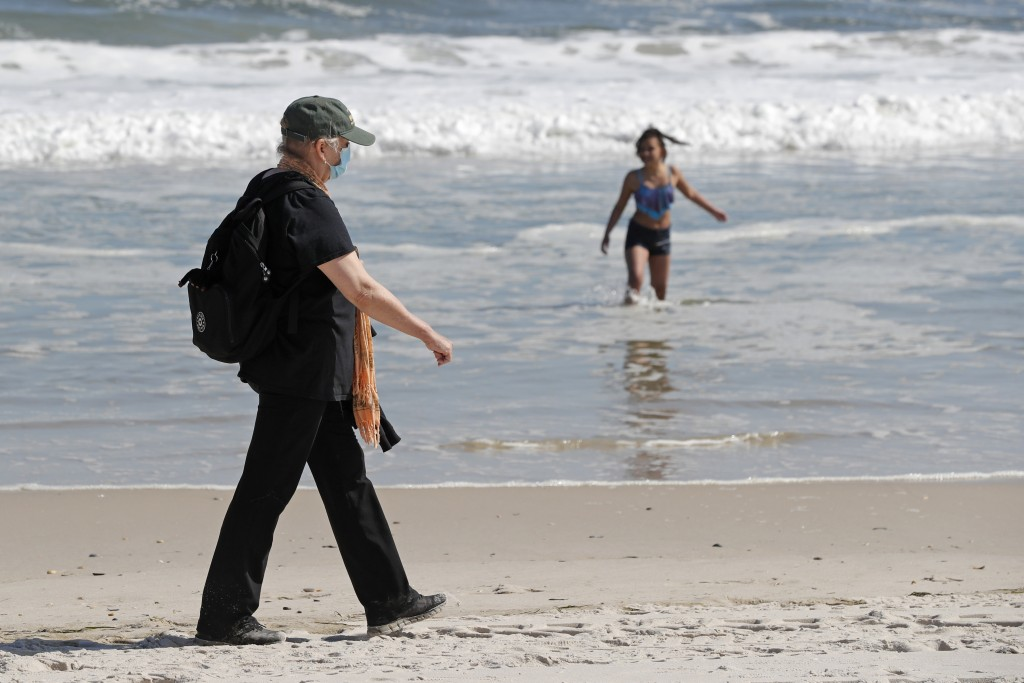 A woman wears a protective face mask during the current coronavirus outbreak, Thursday, May 21, 2020, as she walks on Jones Beach in Wantagh, New York...