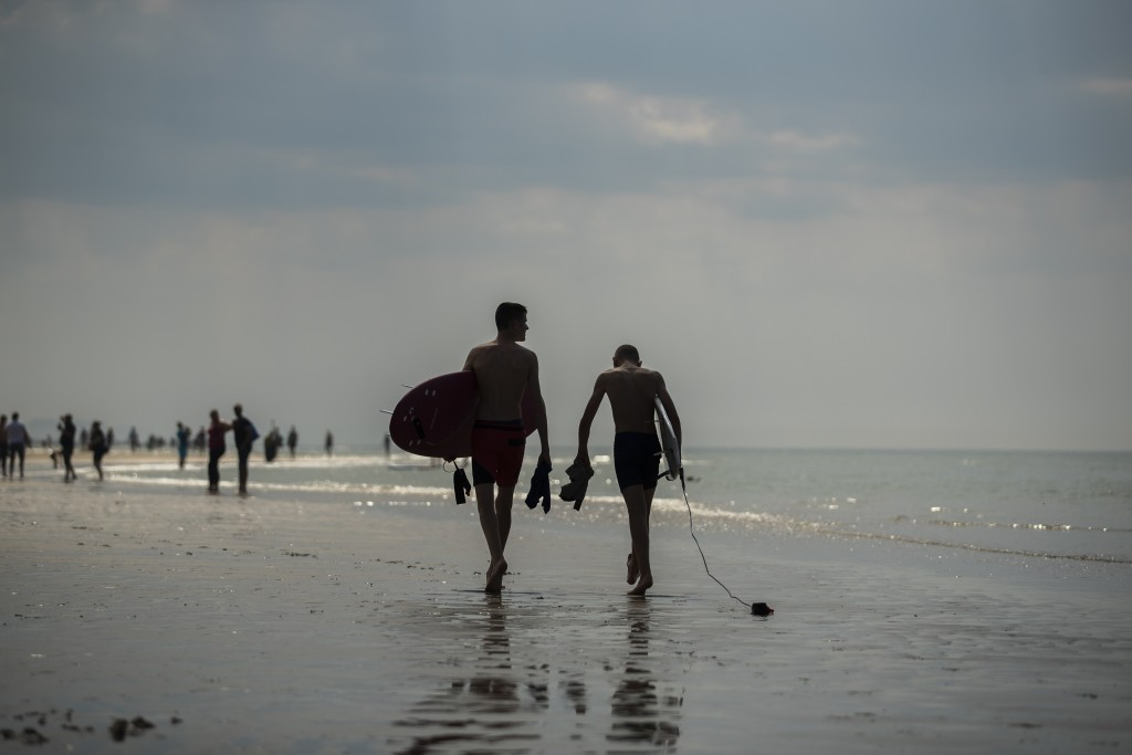 Two surfers walk along the sea shore during a partial lockdown to prevent the spread of coronavirus, COVID-19, in Oostende, northern Belgium, Thursday...