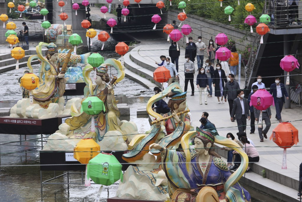 People walk as traditional lanterns with Buddhism-inspired themes are displayed at the Cheonggye Stream in Seoul, South Korea, Friday, May 22, 2020. S...