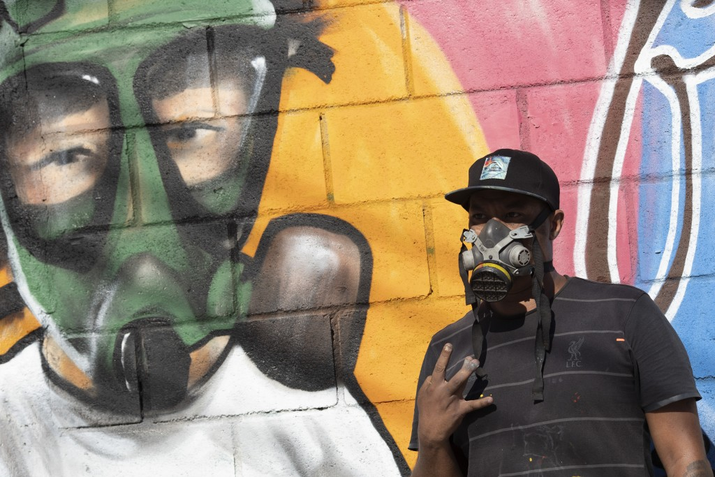 Graffiti artist Angelo Campos poses for a photo by his mural referencing the COVID-19 pandemic which he said he painted in honor of health workers in ...