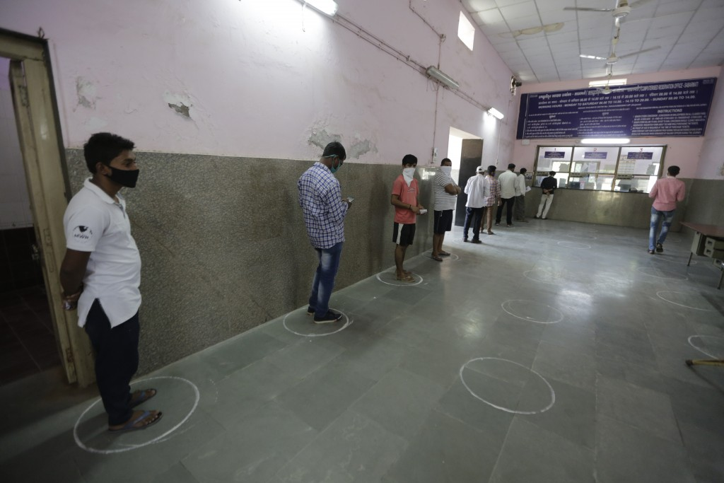 Indians stands in marked positions to observe social distancing as they wait to buy tickets at Sabarmati Railway station during a nationwide lockdown ...