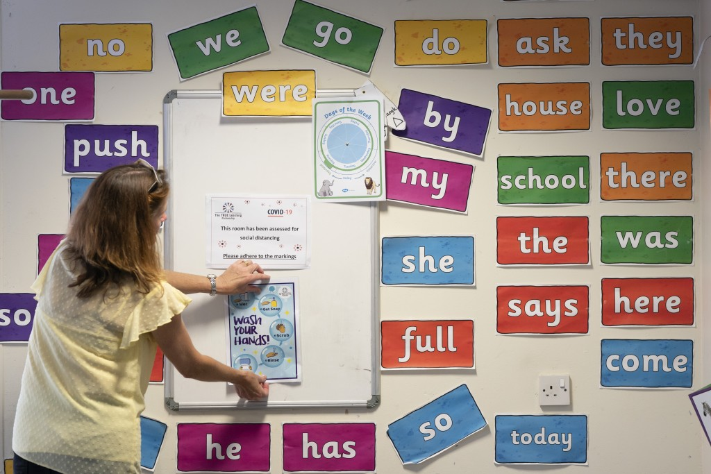 Reception teacher Elizabeth Dockry places signage in a classroom as measures are taken to prevent the transmission of coronavirus before the possible ...