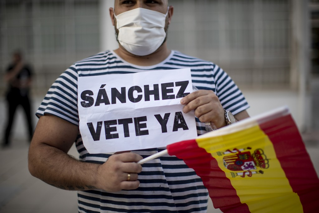 """A man holds a Spanish flag and banner reading in Spanish: """"Sanchez go away"""" during a protest against the Spanish government amid the lockdown to preve..."""