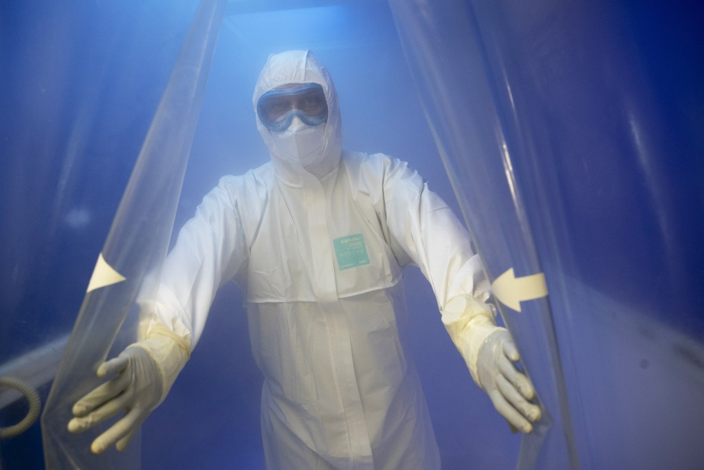 In this photo taken on Saturday, May 16, 2020, Dr. Osman Osmanov walks through a disinfectant sluice after his shift at an intensive care unit of the ...