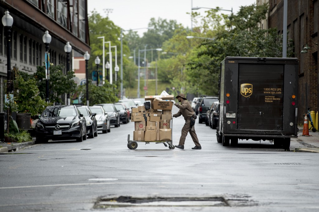 In this May 22, 2020, photo, a delivery man pushes a cart full of packages to deliver to an apartment building on an almost empty street in the Shaw n...