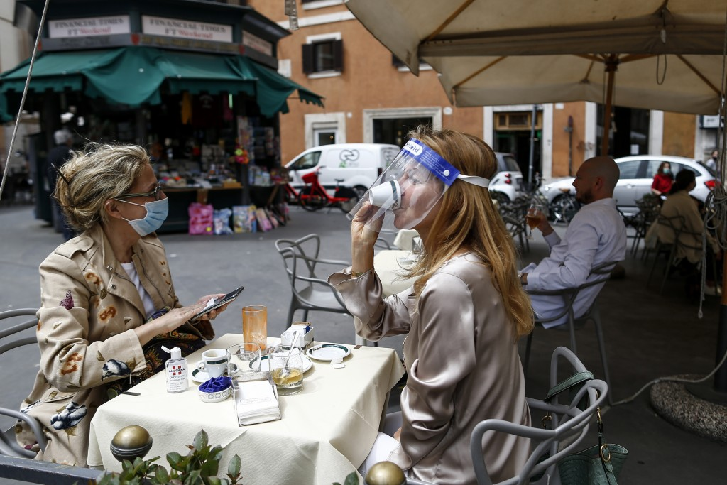 A woman sips coffee under her face sheild at a cafe with outdoor tables in Rome Monday, May 18, 2020. Italy is slowly lifting restrictions after a two...