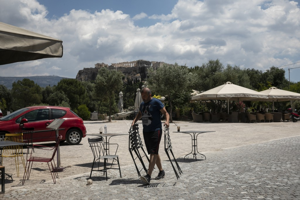 A man carries chairs at an exterior area of a coffee shop being prepared for reopening, in Athens, on Saturday, May 23, 2020. Restaurants and cafes ar...