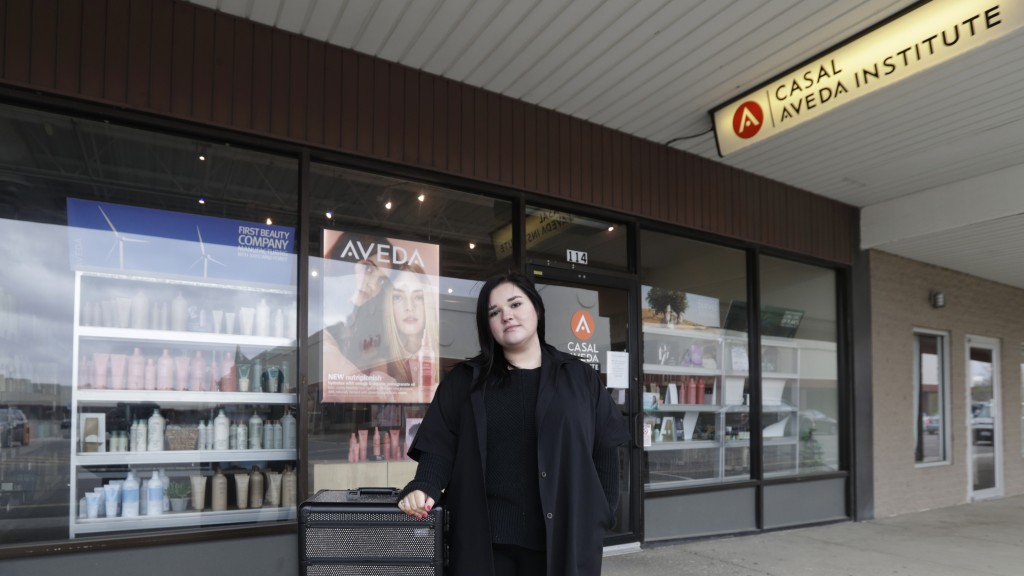 In this Friday, May 8, 2020 photo, Christa Schall poses outside her cosmetology school, Casal Avedo Institute, in Austintown, Ohio. More than 8 millio...