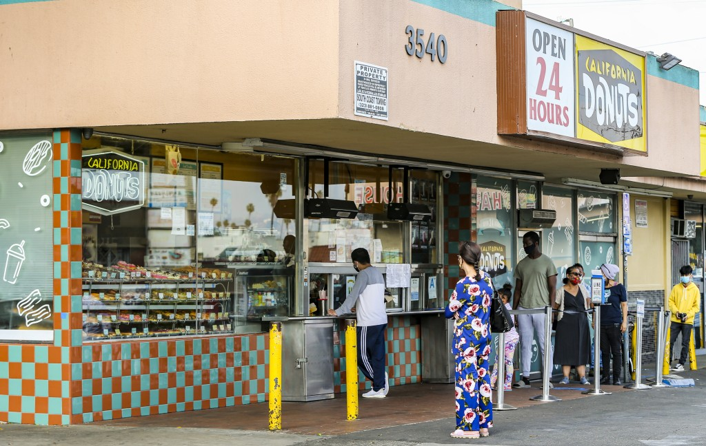 People wear face masks as they line up outside the California Donuts retro-style bakery to purchase donuts in Los Angeles, Friday, May 22, 2020. Milli...