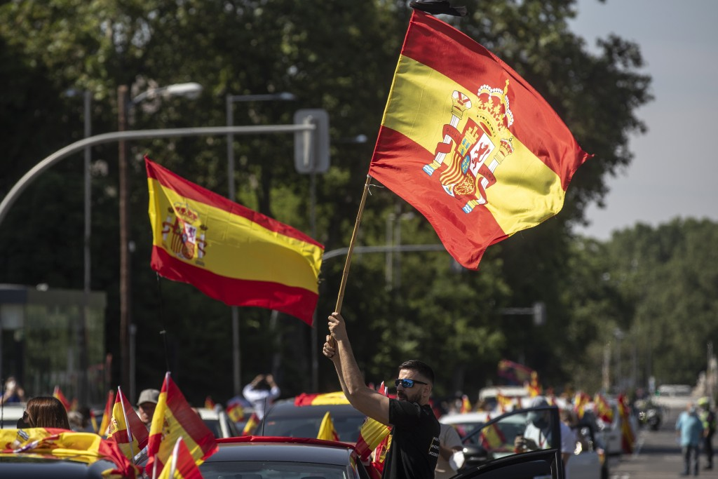 People wave Spanish flags during a drive-in protest organised by Spain's far-right party Vox against the Spanish government's handling of the nation's...