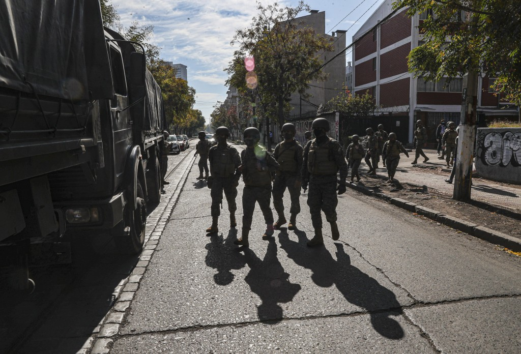 Soldiers patrol as city workers deliver boxes of food during a mandatory quarantine ordered by the government amid the new coronavirus pandemic in San...
