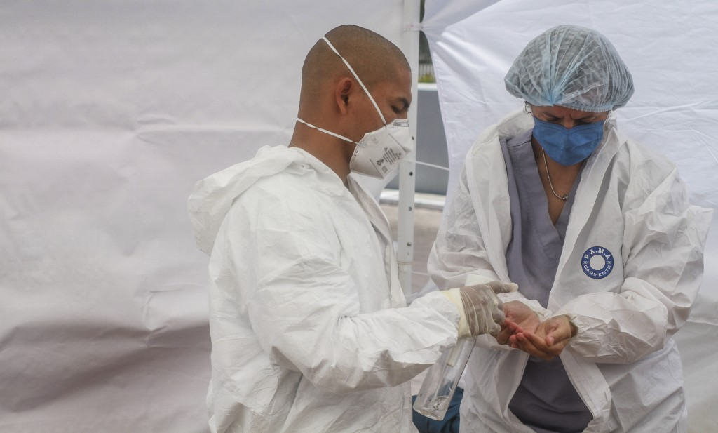 In this May 13, 2020 photo, Dr. Michel Martinez, right, sanitizes her hands before putting on medical gloves, as part of a sanitation protocol, before...