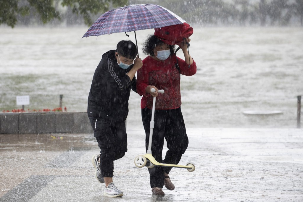 Visitors wearing masks to curb the spread of the coronavirus takes shelter from a sudden rainstorm at a park in Beijing on Saturday, May 23, 2020. New...
