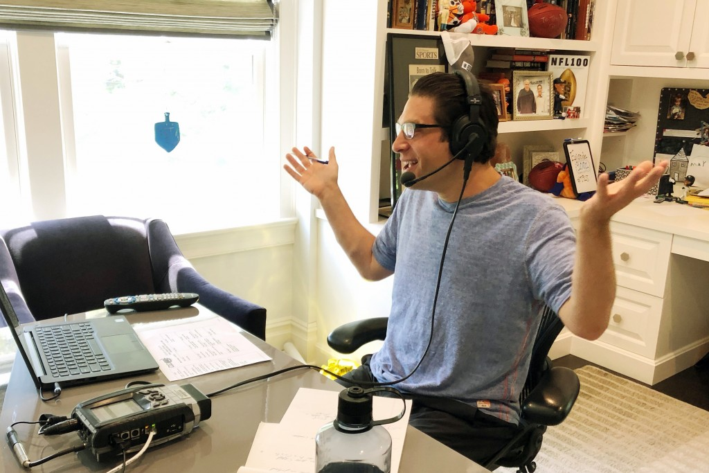 In this May 2020 photo provided by Adam Schein, SiriusXM satellite radio host Schein does his daily radio show from his home in New York. With the cor...