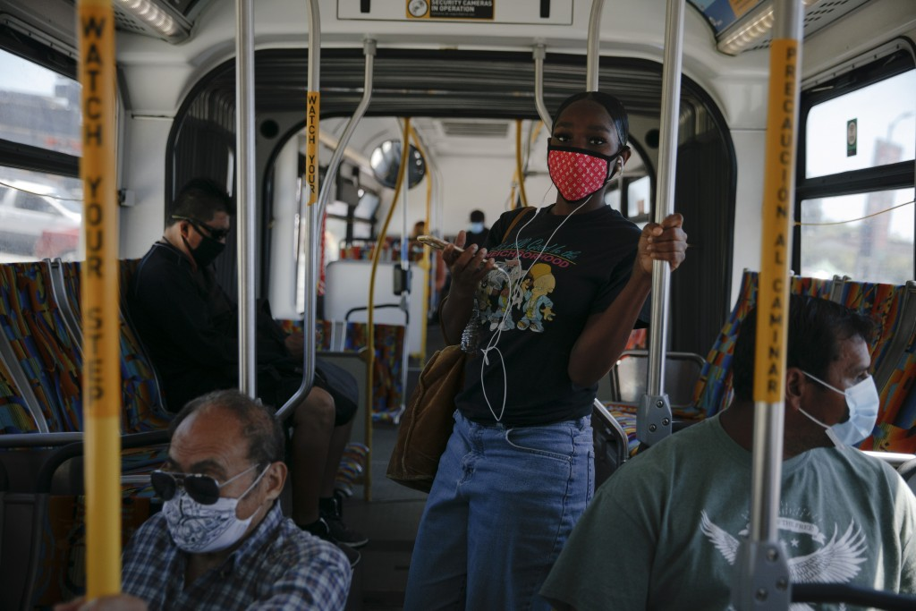 Commuters wearing masks ride a bus during the coronavirus pandemic in the Vermont Square neighborhood of Los Angeles, Thursday, May 21, 2020. While mo...