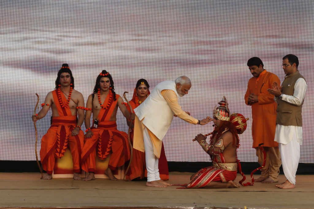 FILE - In this Oct. 8, 2019, file photo, Indian Prime Minister Narendra Modi applies vermilion on the forehead of an artist dressed as Hindu monkey go...