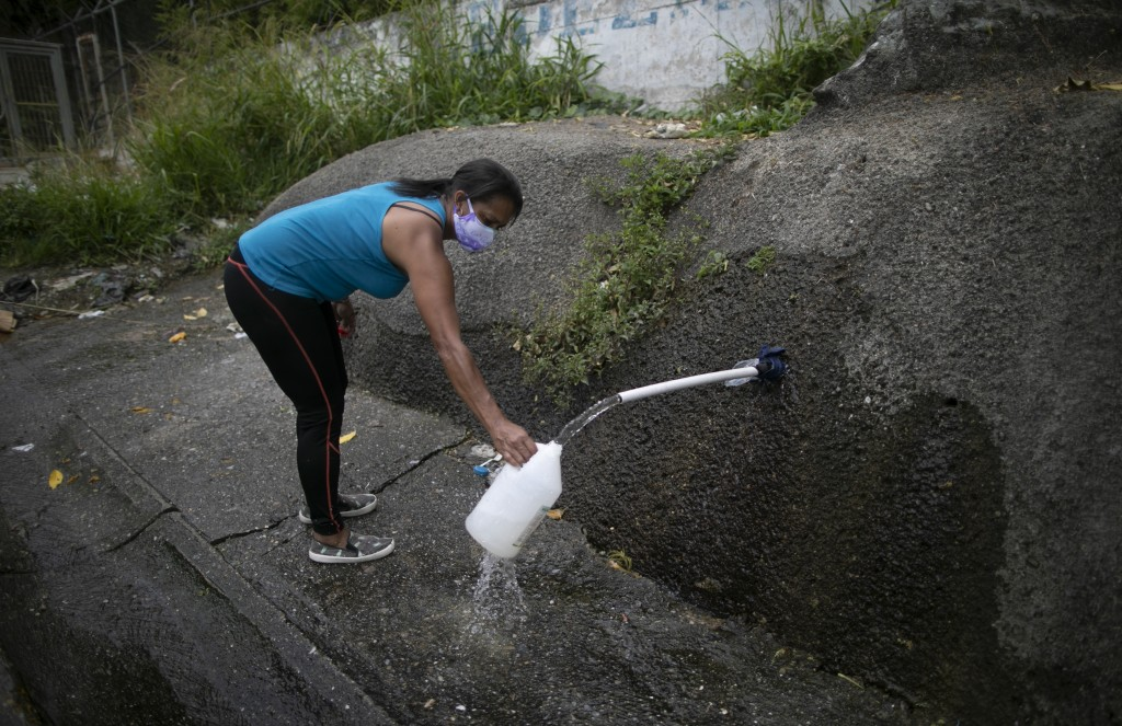 FILE - In this April 22, 2020, file photo, a woman wearing a face mask as a precaution from the coronavirus collects water on the side of the road to ...