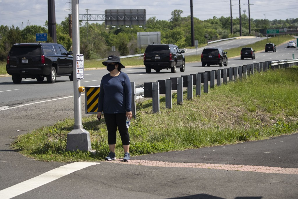 A woman wears a mask as she waits for the motorcade for President Donald Trump to go past, Saturday, May 23, 2020, in Sterling, Va. Trump is en route ...