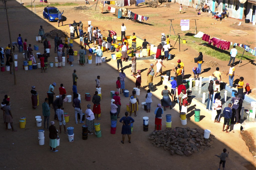 In this April, 24, 2020, photo, people wait to fetch water from a row of communal taps that the group Doctors Without Borders provided in a suburb of ...