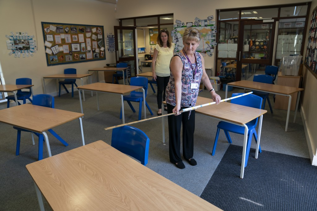 Year 6 teacher Jane Cooper uses a 2 meter length of ruler and pipe to check seat spacings in her classroom as measures are taken to prevent the transm...