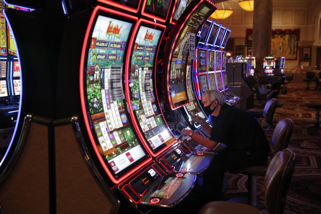A worker works on an electronic slot machine as chairs have been removed from some machines to maintain social distancing between players at a closed ...