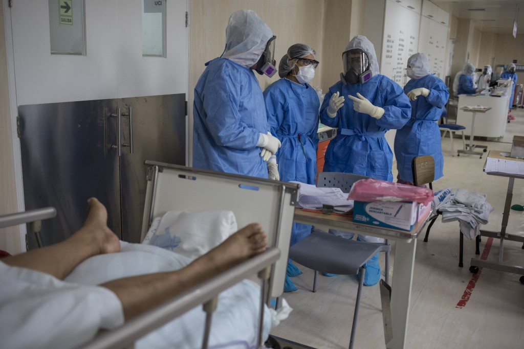 Doctors meet inside the intensive care unit for COVID-19 patients at the Guillermo Almenara hospital in Lima, Peru, Friday, May 22, 2020. Despite stri...