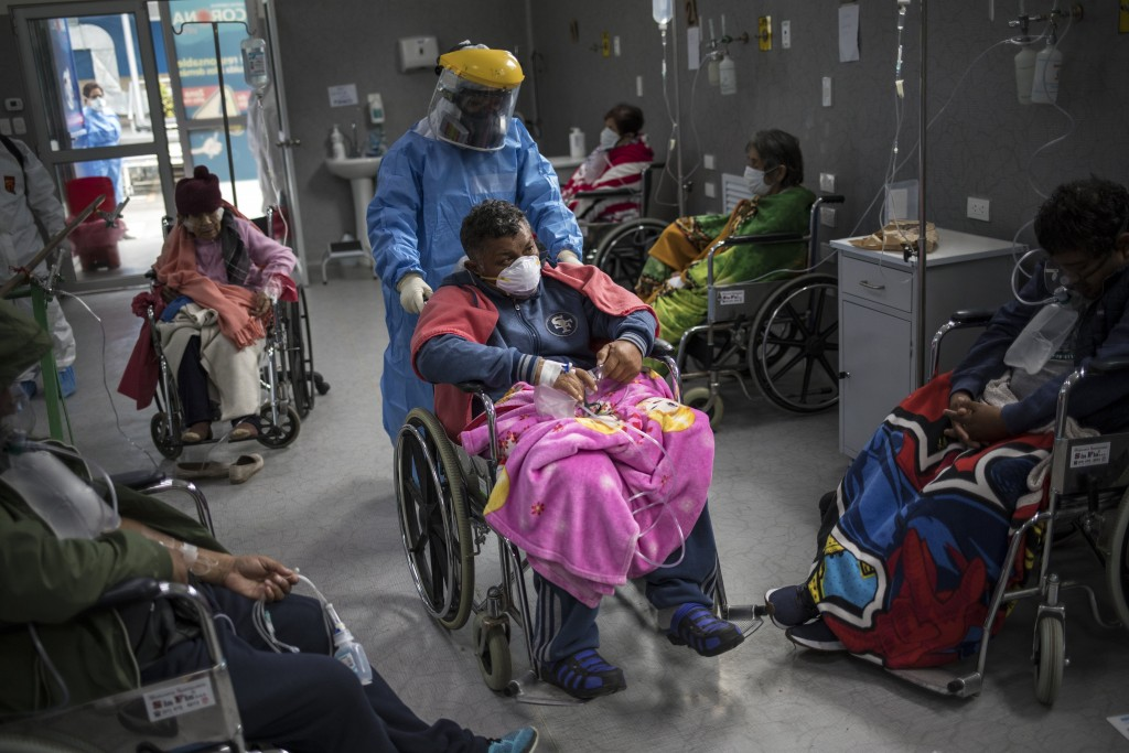 A doctor pushes a COVID-19 patient in a wheelchair in the emergency area of the Guillermo Almenara hospital in Lima, Peru, Friday, May 22, 2020. Despi...