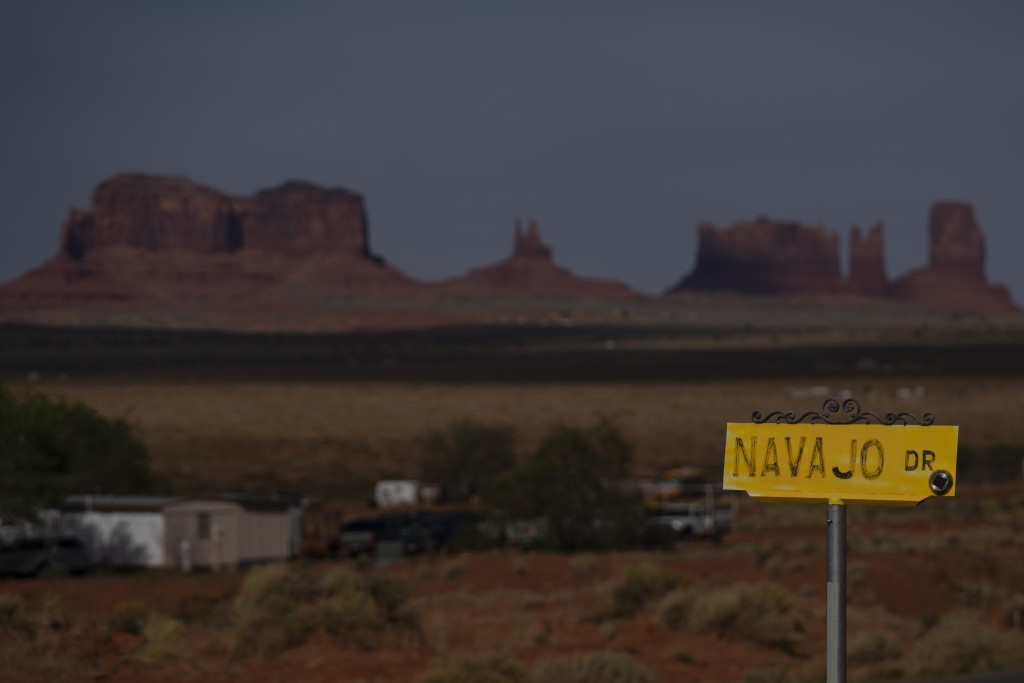 In this April 30, 2020, photo, a sign marks Navajo Drive as Sentinel Mesa, homes and other structures in Oljato-Monument Valley, Utah on the Navajo Re...