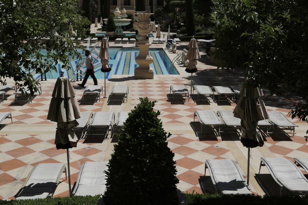 Groups of reclining pool chairs are separated to maintain social distancing between groups as a coronavirus safety precaution at the closed Bellagio h...