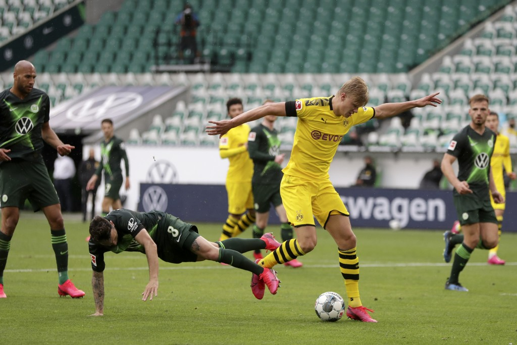 Wolfsburg's Renato Steffen, center left, fights for the ball with Dortmund's Erling Haaland during the German Bundesliga soccer match between VfL Wolf...