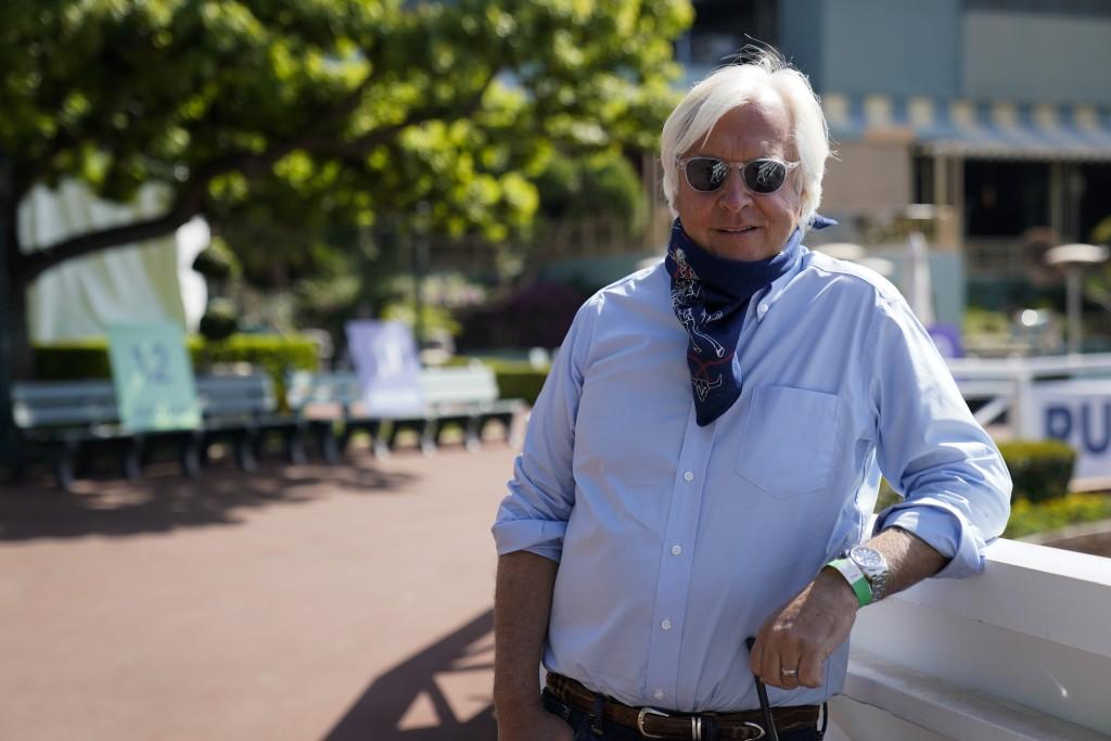 In this Friday, May 22, 2020 photo, Bob Baffert, two-time Triple Crown-winning trainer, lowers his bandana during an interview while keeping his dista...
