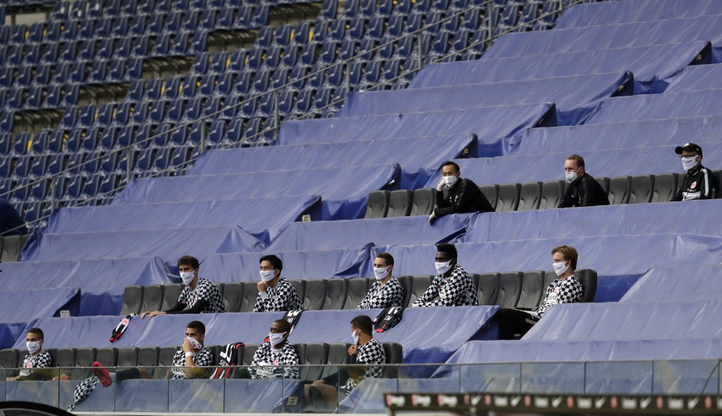 Frankfurt team members, keeping a distance, sit in the stands during the German Bundesliga soccer match between Eintracht Frankfurt and Borussia Moenc...