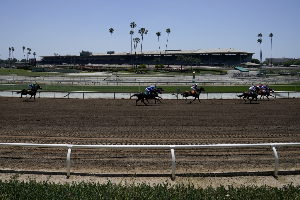 In this Friday, May 22, 2020 photo, jockeys wearing face masks ride in the first horse race past empty stands at Santa Anita Park in Arcadia, Calif. H...
