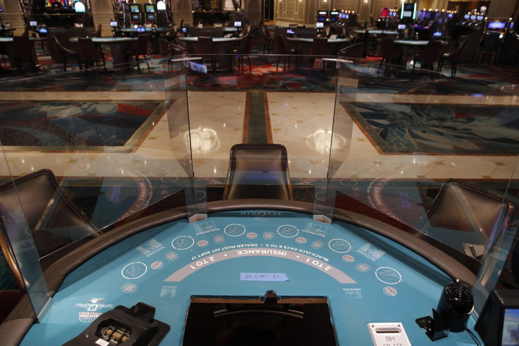 Acrylic barriers separate player's seats as a coronavirus safety precaution at a blackjack table in the closed Bellagio hotel and casino, Wednesday, M...