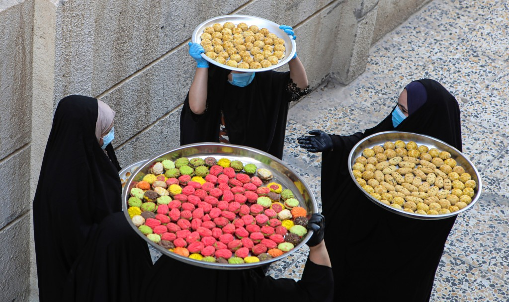 Iraqi women carry cookies for the upcoming Muslim Eid al- Fitr celebrations, that marks the end of the Muslim holy fasting month of Ramadan, in Basra,...