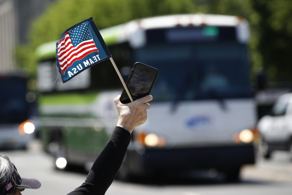 FILE - In this May 13, 2020, file photo, tour guide Barbara Western waves a flag in support of bus and motor coach operators as they circle the Nation...