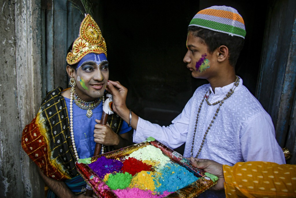 FILE- In this March 7, 2020, file photo, a school boy dressed as Hindu mythological character Krishna has colored powder applied on his face to celebr...