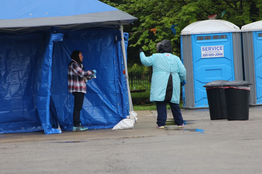 In this May 14, 2020 photo, a woman gets tested at a new testing site in the Little Village neighborhood of Chicago. Chicago's Little Village neighbor...