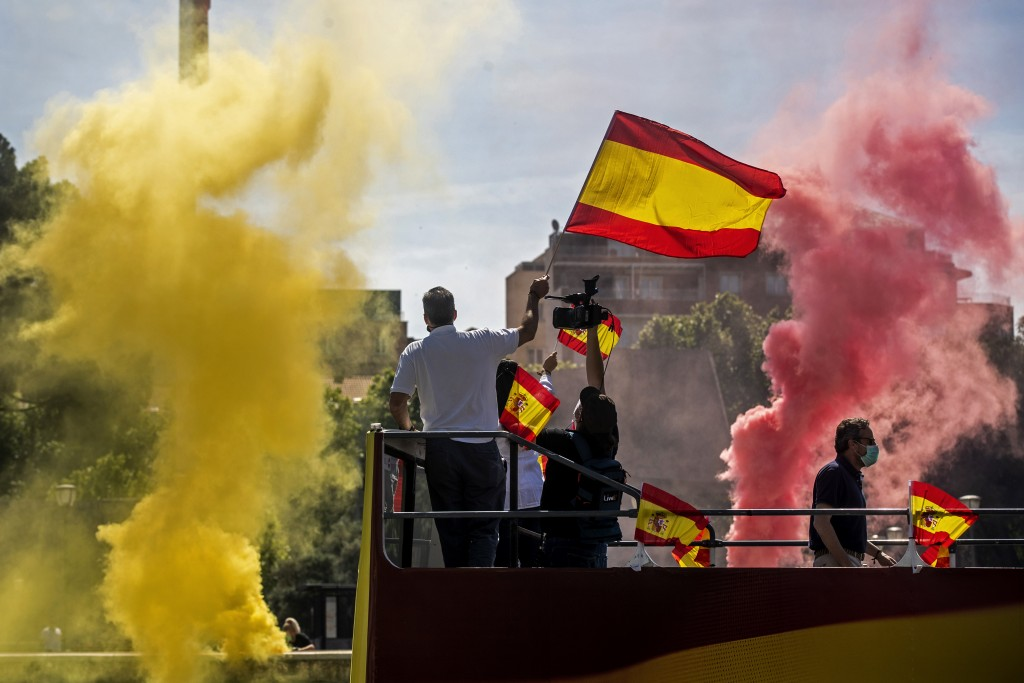 People wave Spanish flags as they burn flares during a drive-in protest organised by Spain's far-right Vox pazrty against the Spanish government's han...