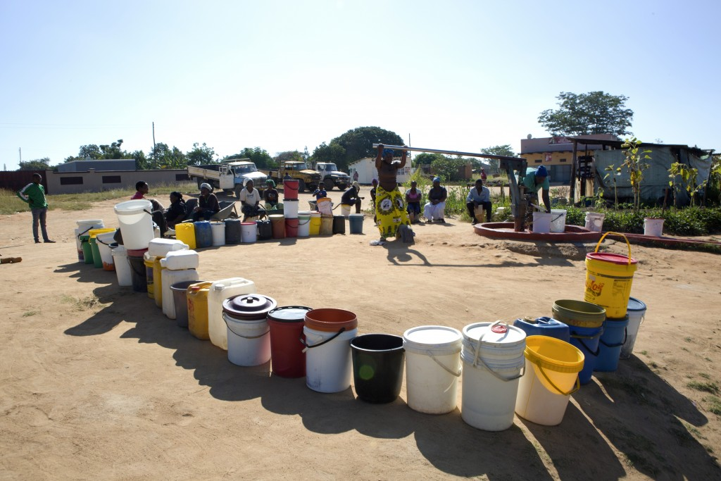 In this March, 31, 2020, photo, buckets are lined up as women fetch water in a suburb of Harare, Zimbabwe. For people around the world who are affecte...