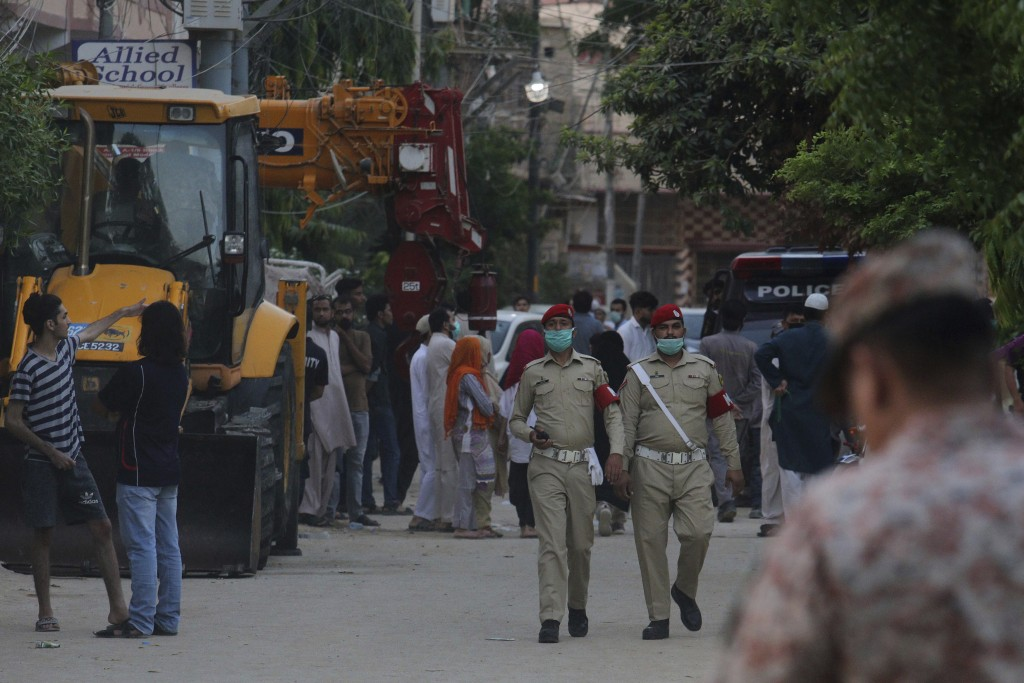 Local residents gather at a street blocked by security officials near the site of a plane crash, in Karachi, Pakistan, Saturday, May 23, 2020. A passe...