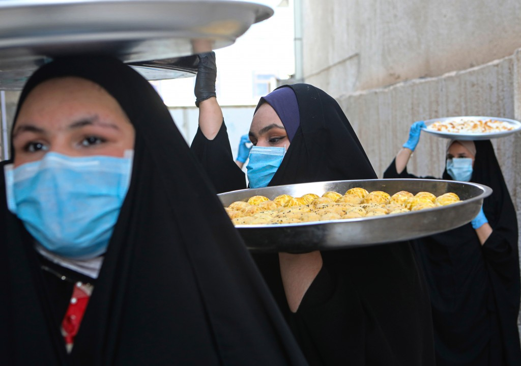 Iraqi women wearing face masks for protection against the spread of the new coronavirus, carry cookies for the upcoming Muslim Eid al-Fitr celebration...