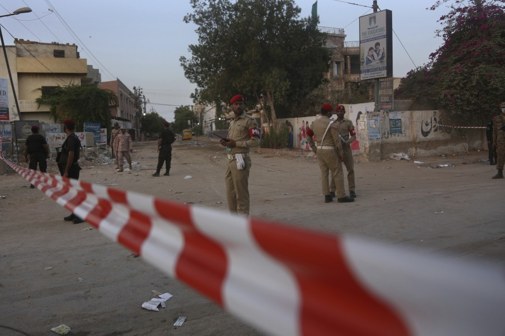 Pakistan army soldiers and police commandos stand guard while they cordon-off a street leading to the site of a plane crash, in Karachi, Pakistan, Sat...