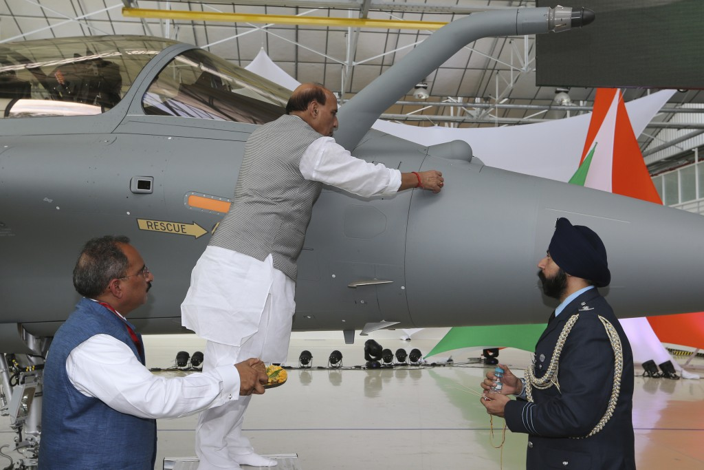 FILE- In this Oct. 8, 2019, file photo, Indian Defense Minister Rajnath Singh writes onto a Rafale jet fighter as a ritual gesture during an handover ...
