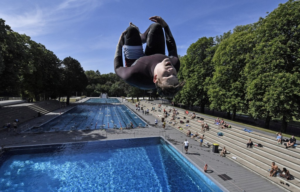 A swimmer jumps into the water during the opening day of the public open air pool in Cologne, Germany, on a warm and sunny Thursday, May 21, 2020. Pub...