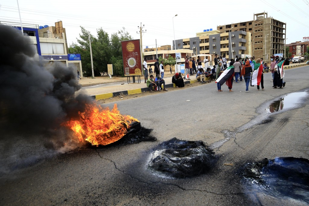 Sudanese protesters carry national flags and burn tyres during a demonstration to commemorate the first anniversary of a deadly crackdown carried out ...
