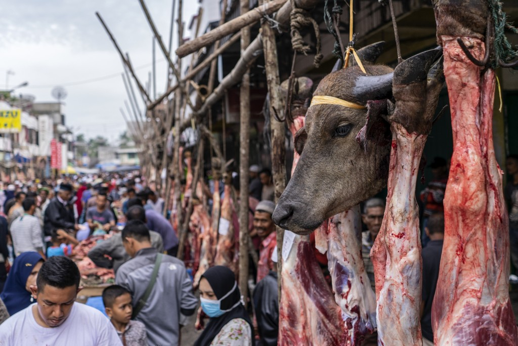 A buffalo's head hangs on a butcher's stall during 'Meugang', a local tradition where people shop for meat one day prior to the Eid al Fitr to be cook...