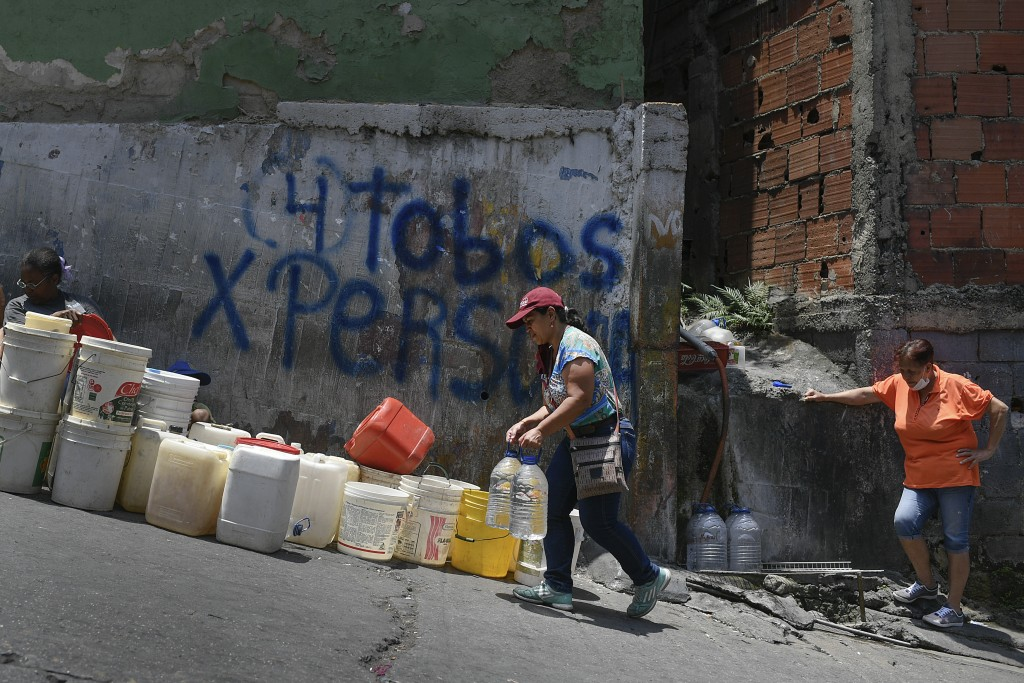 FILE - In this May 9, 2020, file photo, a woman carries containers of water in the Petare neighborhood, one of the poorest slums in Caracas, Venezuela...