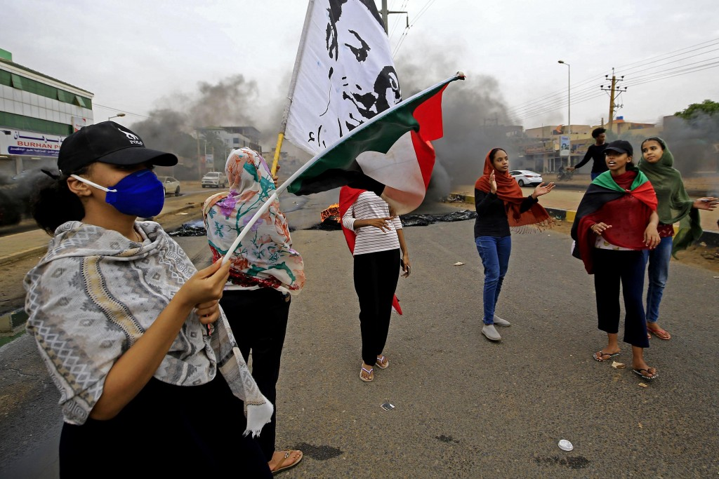 Sudanese women carry national flags during a demonstration to commemorate the first anniversary of a deadly crackdown carried out by security forces o...
